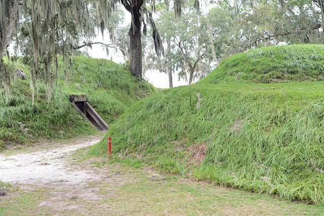 Green earthen fortification mounds of Fort McAllister showing wood-framed entrance