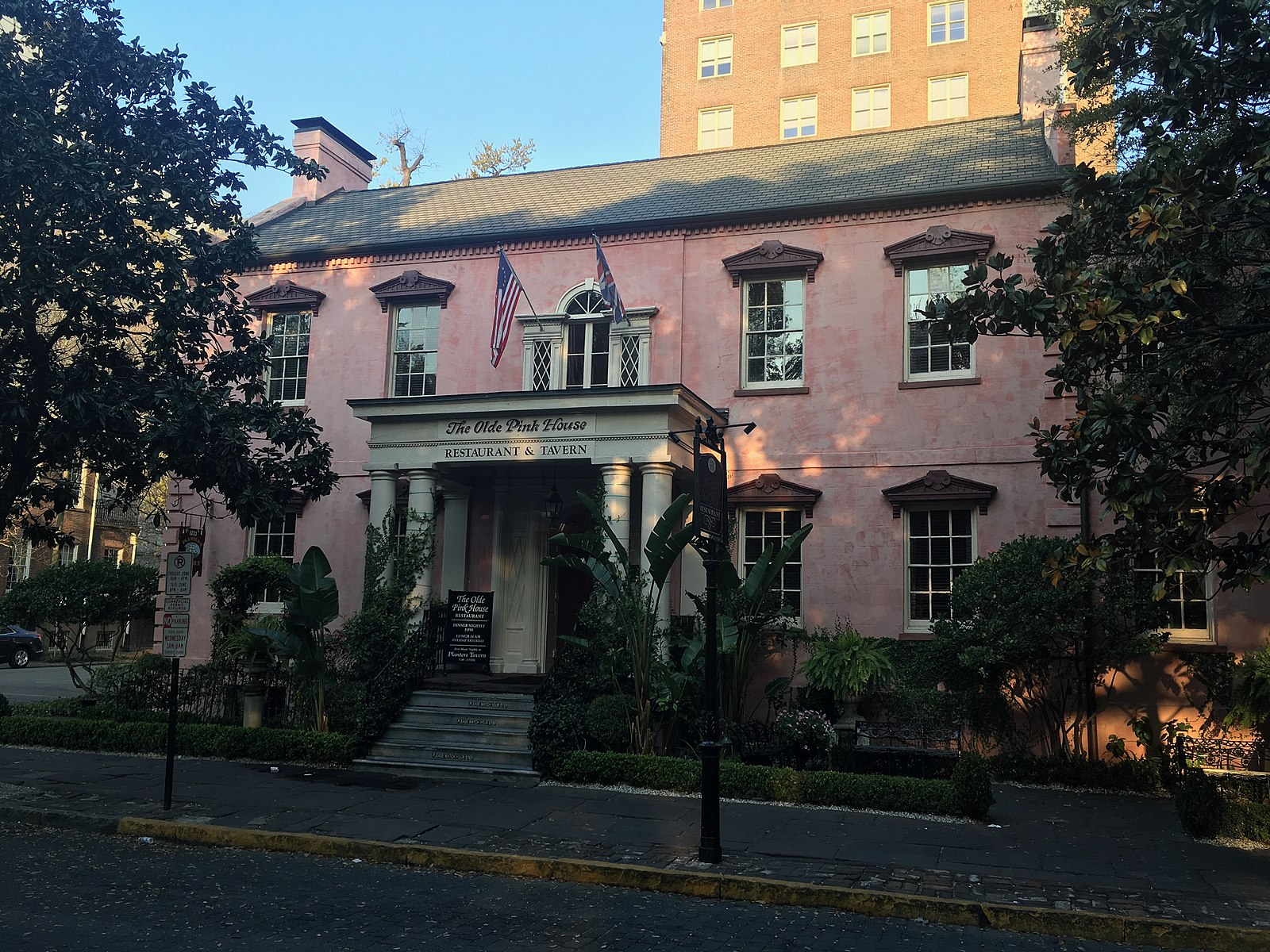 The facade of the Olde Pink House flanked by trees and landscaping.