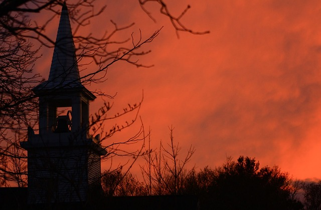Orange sunset over the spire of a house.